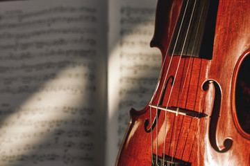 Preparing for a concert. Classic brown violin on music score sheet background. Musical instruments.