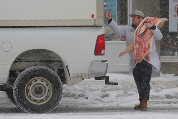 A butcher delivers pork during a snow storm in Toronto