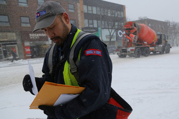 A Canada Post employee delivers mail during a snow storm in Toronto