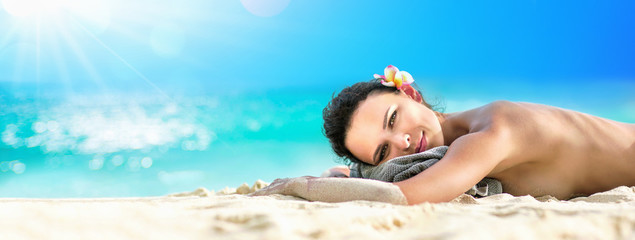 Beautiful Girl Lying Down Under The Sun Tanning In a Tropical Beach