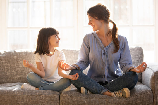 Mindful mom teaching yoga happy child daughter sitting on couch