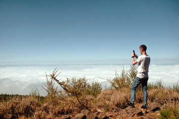 Young tourist taking photo of beautiful mountain landscape with mobile phone. Hiker taking a picture of a beautiful view with clouds and sky.