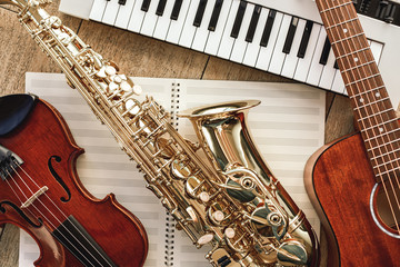 Power of music. Top view of musical instruments set: synthesizer, guitar, saxophone and violin...