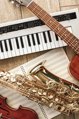Vertical top view of different musical instruments: synthesizer, guitar, saxophone and violin lying...