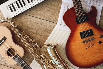 Composition of different musical instruments: synthesizer, electronic guitar, saxophone and ukulele lying, sheets with music notes lying on and wooden floor