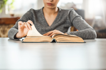 woman reading book on the desk