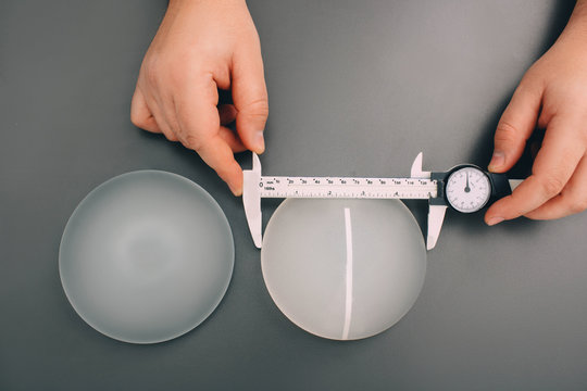 Surgeon measure size silicone breast implants, close-up, view from above. Cosmetic breast surgery.