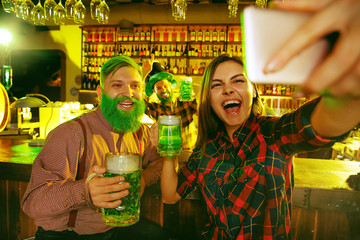 Saint Patrick's Day Party. Happy friends are celebrating and drinking green beer. Young men and women taking selfie photo with phone. Pub interior.