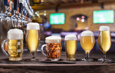 Wall Mural - Chilled mugs and glasses of beer on the old wooden table. Pub interior and bar counter with beer taps at the background.