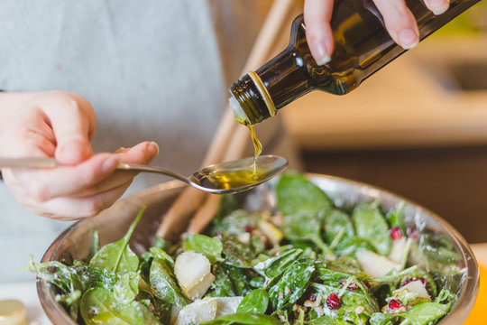 Closeup of hands pouring virgin olive or sunflower oil