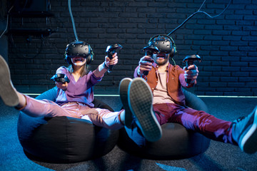 Man and woman shooting with gamepads while playing in virtual reality using VR headsets in the playing room