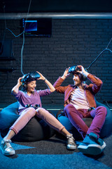 Man and woman with excited emotions sitting together after the game in virtual reality in the playing room