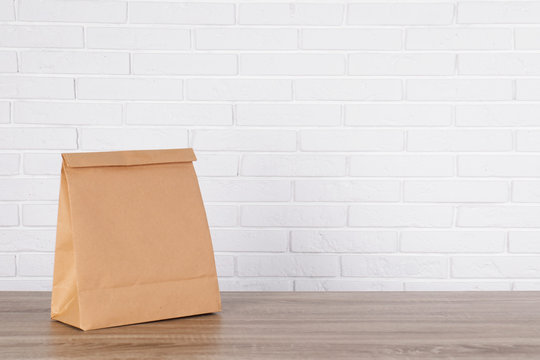 Paper bag on table against brick wall. Mockup for design