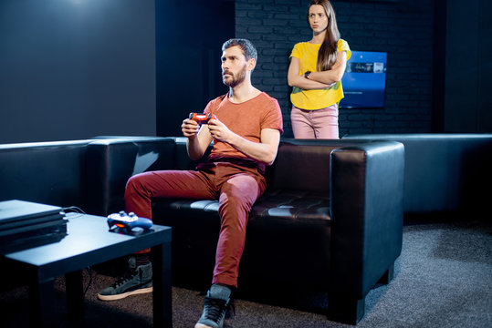 Young woman angry at her boyfriend playing video games with gaming console sitting on the couch at home or playing club