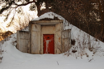 The entrance to the abandoned bomb shelter building is an old door in the concrete wall outside the city in snowy winter day