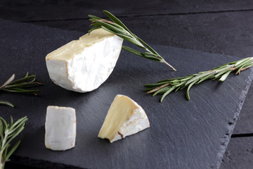 Camembert and rosemary on black stone board. Soft cheese with white mold on black background. Sliced cheese and rosemary branches on slate board