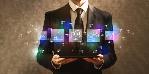 Stock trading concept with businessman holding a tablet computer on a dark vintage background