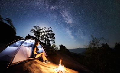 Female hiker having a rest on rocky mountain top beside camp, campfire and tourist tent at summer night, enjoying view of sky full of stars and Milky way. On background starry sky, boulders and trees