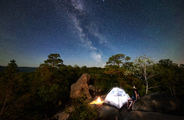 Woman hiker resting on rocky mountain top beside camp, bonfire and tourist tent at summer night, enjoying view of sky full of stars and Milky way. On background starry sky, big boulders and trees