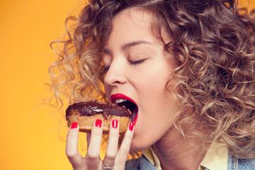 girl bites chocolate donut