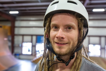 Portrait of a man with dredlocks and a helmet at an extreme sports park