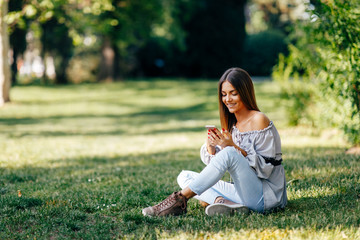 Young woman using a smartphone in the park