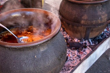 Preparing food outdoor for many people, direct on fire in a big pot.