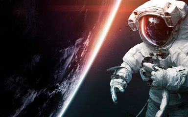Wall Mural - Astronaut at spacewalk. Science fiction art. Elements of this image furnished by NASA