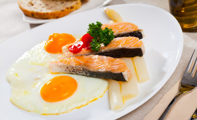 Delicious grilled salmon with eggs, tomatoes, asparagus and parsley