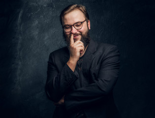 Bearded hipster picks his nose and smiles on a black background in the studio