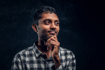Close-up portrait of a handsome young Indian guy wearing a checkered shirt holding hand on chin and looking at a camera with a pensive look.