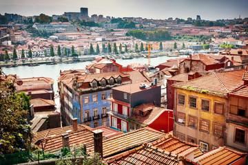 Blick auf Häuser der Altstadt von Porto, den Fluss Douro und die Portwein-Lagerhallen am anderen Flussufer