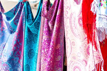 Nahaufnahme von farbenfrohen, portugiesischen Stoffen und Tüchern in türkis, rosa und lila Farben