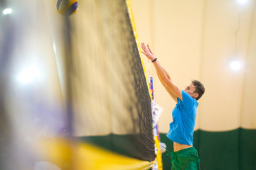 the guy is playing volleyball in a covered room with sand. the volleyball ball over the net