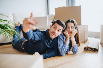 A young couple with a smartphone moving in a new home, taking selfie and making a face.