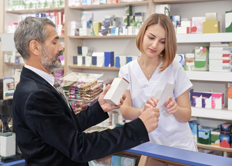 Woman working in drugstore with male client.