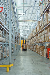 large modern warehouse with forklifts, shelves with pallets, boxes, containers and goods