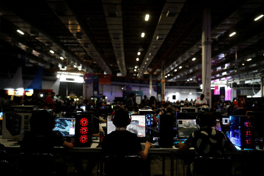 Men play on their computers during the Campus Party, internet users gathering, in Sao Paulo