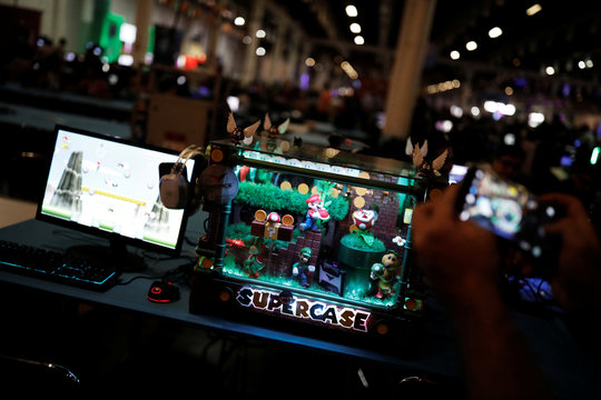 A man takes a picture of a customized computer during the Campus Party, internet users gathering, in Sao Paulo