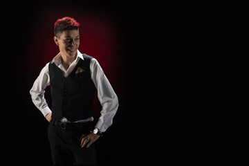Woman with red hair in a black suit and white shirt posing on a black background