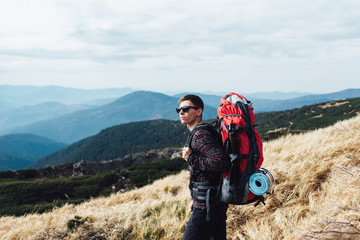 Tourist with a huge backpack on top of a mountain range.