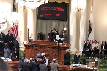 California governor Gavin Newsom embraces state assembly speaker Anthony Rendon as Senate Pro Tem Toni Atkins looks on at the California State Capitol in Sacramento
