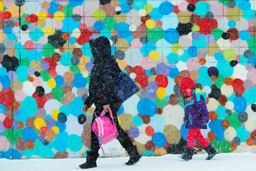 A woman and child walk through a winter snow storm in Boston