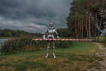 Knight in full armor with a sword against the background of a lake and an old castle