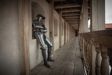 Knight in full armor with a sword against the background of the ancient walls of a brick castle