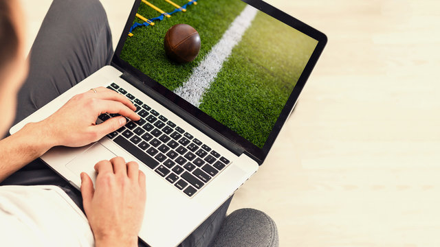 man use mobile Computer , blur image of football match on screen.