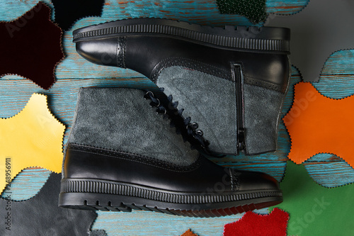 Shoe making concept with mens boots over brown background