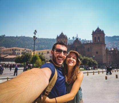 handsome happy tourist couple taking selfie in Plaza de Armas with Inca fountain, Cathedral and Compania de Jesus Church, city of Cusco, Peru