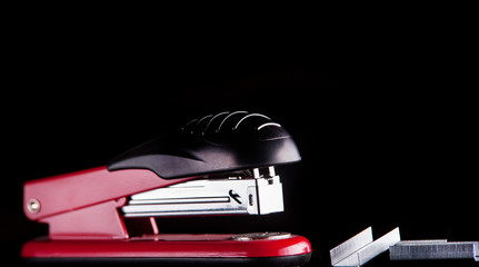 red stapler with staples on a black background