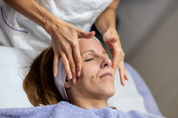 Young woman getting a rejuvenating face massage